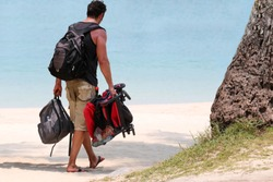 Tourists man are walking, holding a baby strollers and luggage on the white sand  beach, Parenting and travel concept.