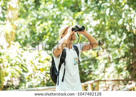 Tourists man with Binoculars Looking for something along the forest #1047482128