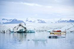 Tourists on amphibious vehicle taking a cruise around the Jokulsarlon glacier lake, where icebergs melting from the Vatnajokull glacier and float out to the Atlantic ocean