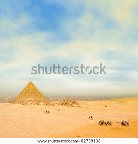 Tourists on camels through the desert go to the pyramid.