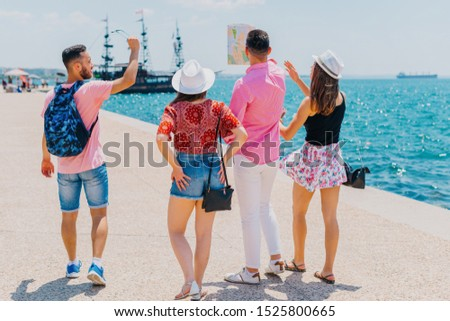 Tourists reading a map and wondering if they are at the right spot while looking at an anchored pirate boat. Tourists wandering around in a touristic city with a sea view