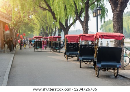 Tourists riding Beijing traditional rickshaw in old China Hutongs in Beijing, China. Landscape and culture travel, or historical building and sightseeing concept