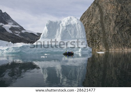 Tourists sailing next to an iceberg in the high arctic (Greenland)