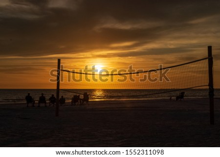 Tourists sit on the beach and watch the sunset with empty vollebyall net in foreground along Gulf of Mexico on Fort Myers Beach, FL