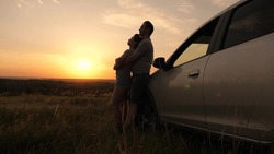 Tourists travel by car, hug, admire sunrise, nature. Free travelers, tourists. Happy enamored travelers man and woman stand next to car and admire beautiful sunset at campsite. Family travel by car.