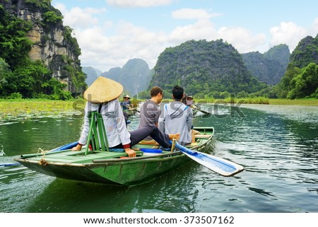 Tourists traveling in boat along the Ngo Dong River at the Tam Coc portion, Ninh Binh Province, Vietnam. Rower using her feet to propel oars. Scenic landscape formed by karst towers and rice fields.