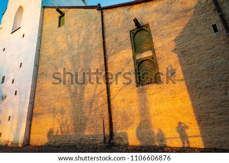 Tourists, tree and photographer casting shadows on sunset colored historical building of The Cathedral of Saint Mary the Virgin in Tallinn Old Town, Estonia #1106606876