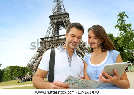 Tourists using electronic tablet in front of the Eiffel tower