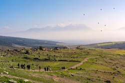 Tourists walk along mountain trail surrounded by green grass and rocks with views of snow capped mountains covered with clouds and lots of flying balloons in sky in sunny weather in Pamukkale, Turkey