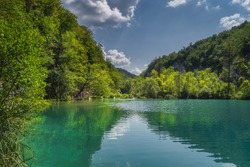 Tourists walking on footpath under trees with a view on turquoise lakes and waterfalls. Plitvice Lakes National Park UNESCO World Heritage, Croatia