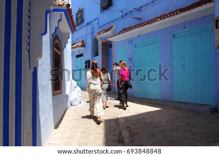 Tourists walking on the narrow streets of The Blue City in Marocco. Group of people visiting the blue streets of Chefchaouen. Women walking on an alley with colorful buildings and doors in Morocco
