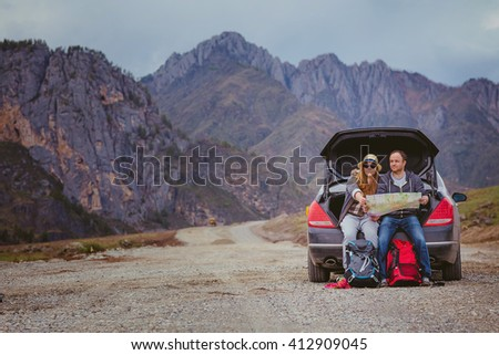 Tourists with a map and backpacks in the car in the mountains