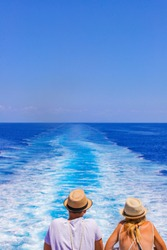 Tourists with a straw hat stand on the deck of a cruise ship and look out over the ocean  While the boat is sailing. A man and woman are looking at the sea as they stand at the edge of the ship's deck