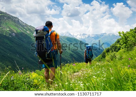 Tourists with hiking backpacks in mountain hike in Svaneti on summer day. Young guys go along the footpath through the mountains of Georgia. Tourists in beautiful mountain landscape.