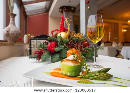 tournedos of Chilean sea bass with salmon with green herb sauce on the steam asparagus with poached quail in a festive New Year's serving in the interior of the restaurant and glass of wine