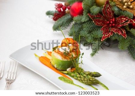 tournedos of Chilean sea bass with salmon with green herb sauce on the steam asparagus with poached quail in a festive New Year's serving in the interior of the restaurant and glass of wine - stock photo