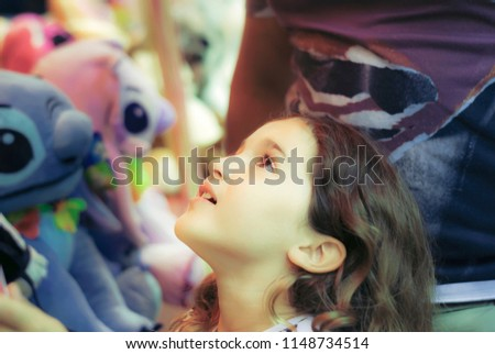 Tournon-sur-Rhône, France - July 22, 2018 : Litlle girl looking up to stuffed toys with a child' s eyes in a funfair. #1148734514