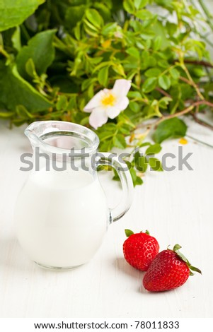 Tow fresh strawberries and jug of milk on white table with green leafs and wild rose as background