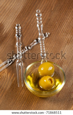 Tow green olives with olive oil in little glass bowl