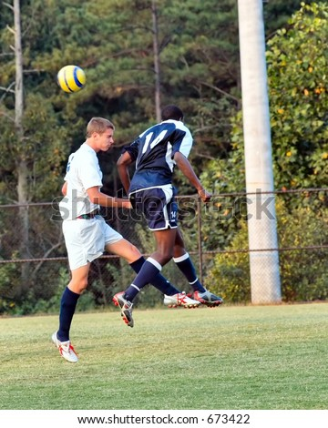Tow male soccer players try for the header
