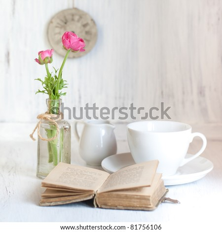 Tow pink flowers ranunculus in old vintage bottle, old opening book and cup of tea on white wooden table