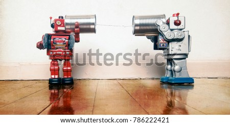 tow retro robots talk on tin can phones on an old wooden floor with reflection