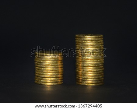 Tow stacks of golden coins in ascending order against dark background. Grooved edge of coins reveals they are authentic. Growth of economy, concept.