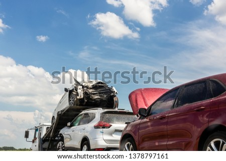 Tow truck trailer on highway carrying three damaged cars sold on insurance car auctions for repair and recovery.  Vehicles shipment and rescue service #1378797161