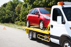 Tow truck with broken car on country road. Space for text