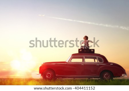 Shutterstock Toward adventure! Girl relaxing and enjoying road trip. Happy child girl sitting on roof of vintage car.