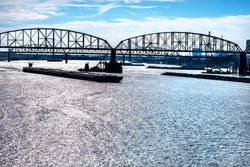 Towboat pushing dry bulk cargo barge under bridges up Mississippi River. Shipping grain corn during harvest season, cargo, food, raw, transportation, agriculture, agricultural, tow, marine, maritime