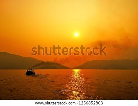 towboat with sun reflex water in Bhumibol dam, Tak, Thailand