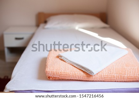 Towel and bedding on a single bed in hostel or guest house room, no reservations guests or visitors, empty no people due to outbreak of deadly Coronavirus (COVID-19) global pandemic crisis, cancelled