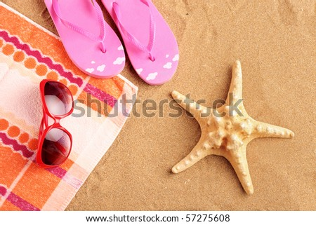 Towel, sandals, sunglasses and starfish at beach