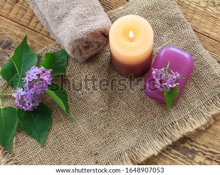 Towel, soap for bathroom procedures, burning candle and lilac flowers on sackcloth and old wooden boards. Top view. Spa products and accessories.