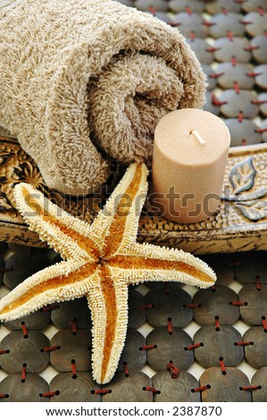 Towel, starfish, candle on a wooden mat