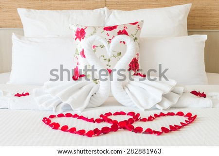 Towel swans and rose flower on bedroom for honeymoon couple - selective focus point