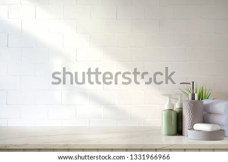 Towels and ceramics shampoo or soap on top marble table in bathroom background.