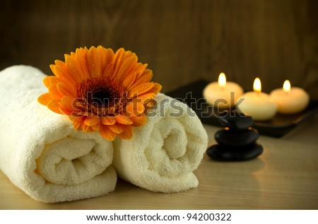 Towels and orange flower, candles and massage Stones in a Zen Spa.