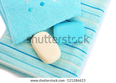 Towels and soaps on white background.