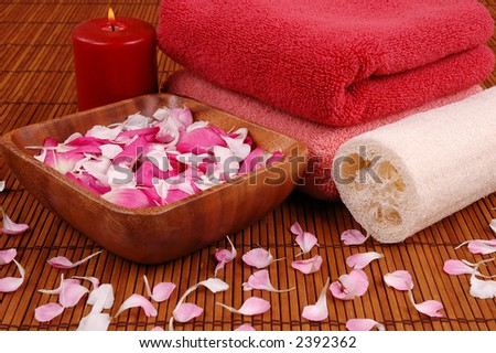 Towels, candle, carnation and rose petals, and bath sponge in a spa