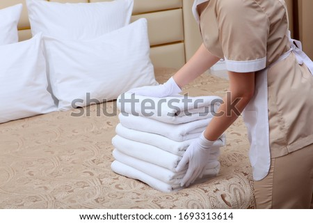 Towels in the hands of the maid. Unrecognizable photo without a face. Cleaning the hotel room. Copy space. The concept of the hotel business.