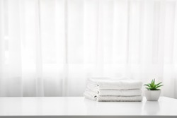 Towels on white wodd top table with copy space on blurred bathroom background. For product display montage.
