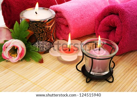 Towels, soap, candles and flower on mat background.