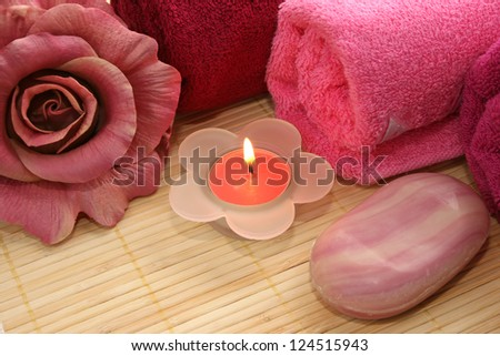 Towels, soaps and flower on mat background.