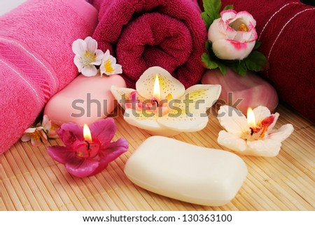 Towels, soaps, flowers and candles on mat background.