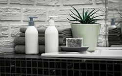 Towels with Liquid Soap on Table in Bathroom.  Mockup for Bathing Products in the Bathroom. Spa Shampoo, Shower Gel, Liquid Soap. Beauty Care Accessories for Bath.