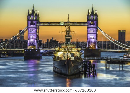 Tower Bridge and HMS Belfast  at sunrise in London, England