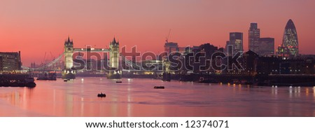 Tower Bridge and the City of London as viewed at sunset along the Thames - stock photo