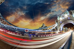 Tower Bridge in London at dusk, fisheye view with car light trail and city in the background